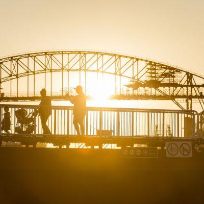 Una familia con niños en sillaita de paseo cruza un puente durante una excursión. La sillita de paseo de segunda edad seguro que tiene instalado el sistema antivuelco PONNY para olvidarse de los tipicos vuelcos.