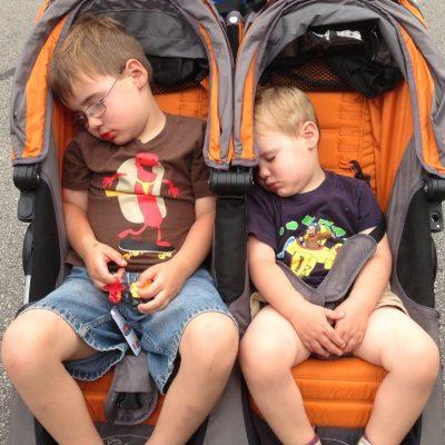 Unos hermanos duermen en una silla de paseo gemelar. Los dos son son mayores.