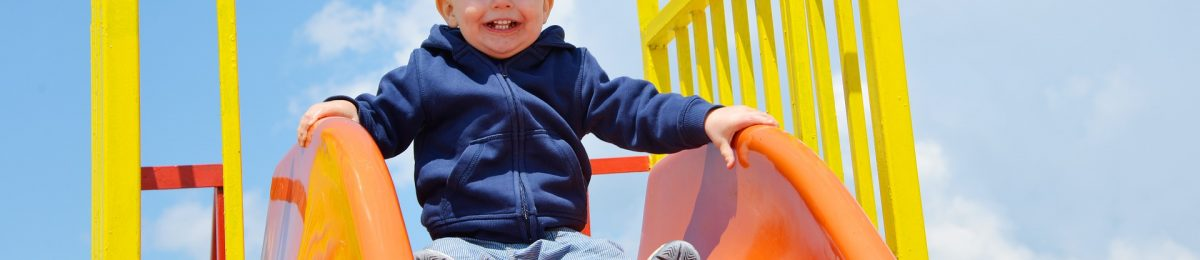un bebé en el parque baja de el tobogán