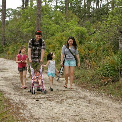 Familia que va de excursión con su silla de paseo y su sistema anticaídas PONNY de PonnyShop instalado para que no vuelque hacia atrás.